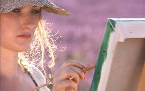 Woman with hat painting a picture